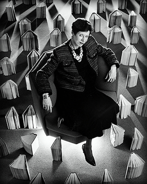 Black & White image of woman surrounded by books in chair.